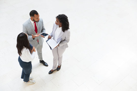Diverse business colleagues discussing work issues in office hallway. Business man and women standing in circle, holding tablet and papers and talking. Corporate meeting concept