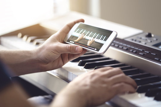 Piano lesson online. Man watching video tutorial with mobile phone and practising playing. Person learning to play an instrument with an internet course and class. Pianist training with smartphone.