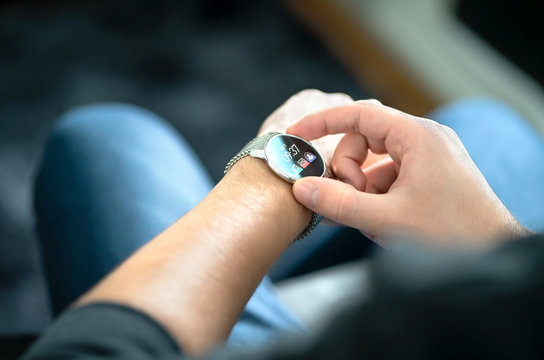 Smart watch, wearable gadget. Man wearing hybrid smartwatch. Wearables with digital touchscreen and mobile app technology. Person using wristwatch for business and work. Device with touch interface.