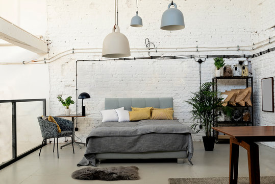 Modern interior of a bedroom with bricky wall in white color and double bed. Loft apartment in scandinavian style.