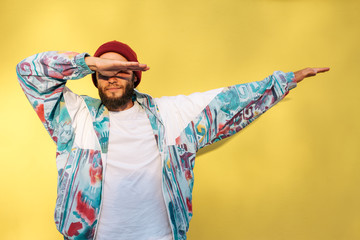 Stylish young hipster man with beard in red hat and a retro jacket of 90s on yellow background.Crazy hipster guy emotions. Collage in magazine style
