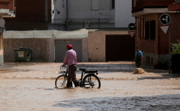 A man walks with his bike through a partially flooded street after heavy rains in San Pedro del Pinatar