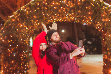 Couple making selfie having fun at Christmas evening