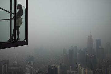 A tourist poses for a picture at Kuala Lumpur Tower with the city skyline in the background shrouded by haze, in Kuala Lumpur