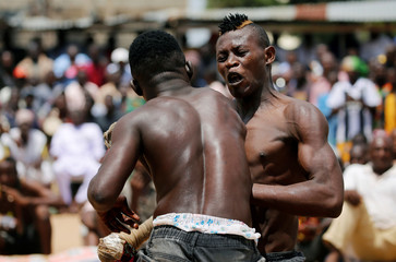 A Dambe boxer reacts as his opponent scores a right-hand blow on his face during a brutal martial art of Dambe boxing, in Dei-Dei, Abuja