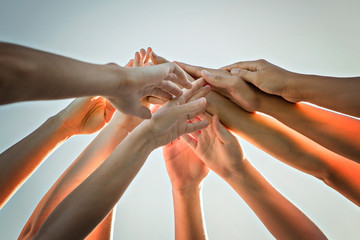 many hands over a nice sky, team work