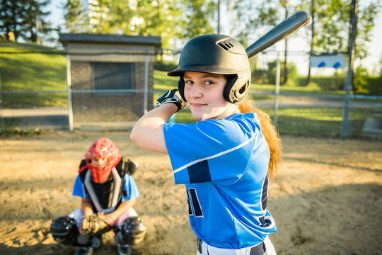 Girl baseball player with bat on the playground