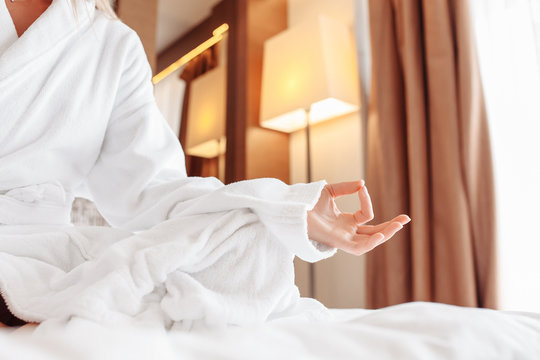 Peaceful calm beautiful young caucasian woman blonde in white coat is meditating with closed eyes while sitting in lotus position on her bed on sunny summer morning. Healthy start to the day concept