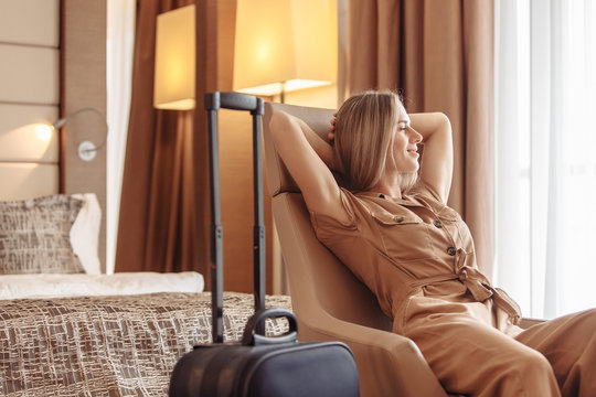 Satisfied smiling young beautiful American European woman relaxes in comfortable chair next to her suitcase while checking into hotel on vacation. Young beautiful woman enjoys a long-awaited vacation