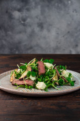 Green salad with steak, aubergine, sunflower sprouds and feta chese in ceramic plate on wooden background