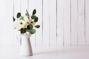 Styled photo of ranunculus and eucalyptus in vase