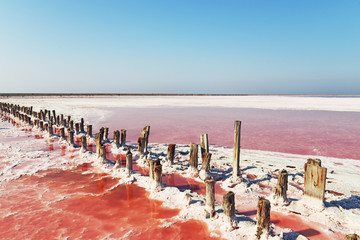 Fotobehang - Unique salt lake with pink water and salt at sunset. Rows of wooden columns covered with salt crystals.