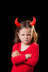 Studio shot of a Cute 5 years old girl with a red devil costume against black background
