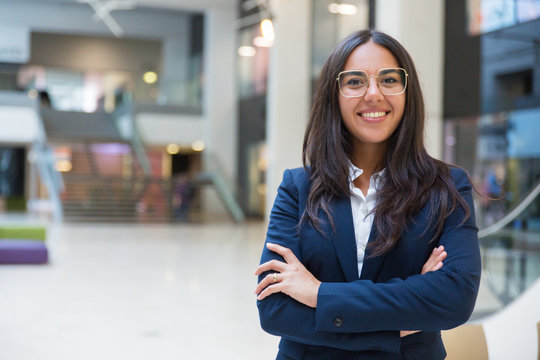 Young businesswoman smiling at camera. Portrait of cheerful Hispanic businesswoman in formal wear standing with crossed arms and looking at camera. Business concept