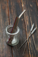 Reusable metal straws in glass jar on wooden table
