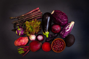 Heap of raw purple vegetables on the black