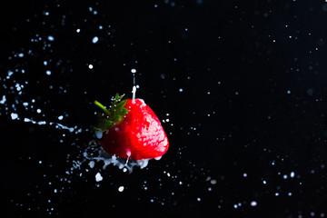 Strawberry fruit close up and milk splashes