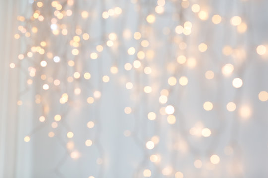 holiday, illumination and decoration concept - bokeh of christmas garland lights over grey background