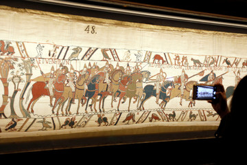 A visitor takes a picture of the Bayeux Tapestry