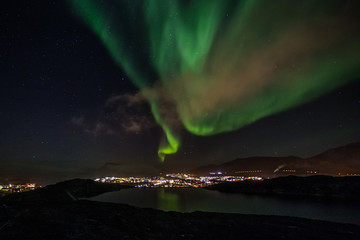Massive green Aurora Borealis Northern lights shining over the lake and Nuuk city, Greenland