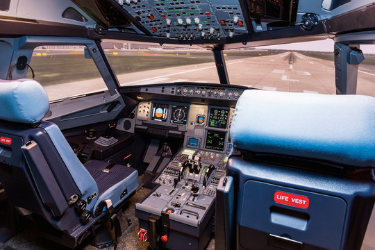 Cockpit of airliner simulator. Switches and dials visible in the background.