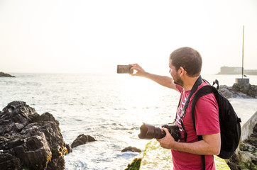 A male photographer taking a selfie on a sunny day at the beach