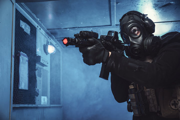 Special unit soldier with gas mask is going out of industrial elevator and aiming a target