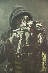 Elite special unit soldier is holding assault rifle and aiming at the target. Studio photos on a concrete wall with a smoke