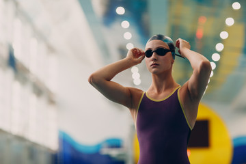 Young woman swimmer getting ready for competition and swim in swimming pool