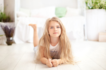 Childhood concept. The child plays in the children's room. Little blonde girl in pajamas at home. time for sleep and rest. Baby girl in a cozy Scandinavian bedroom. The child lies on the floor at home