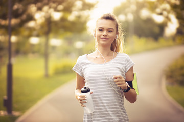Young woman running in park and listening to music with headphones - Beautiful blonde and fit girl jogging alone outdoor in early autumn season - Front view