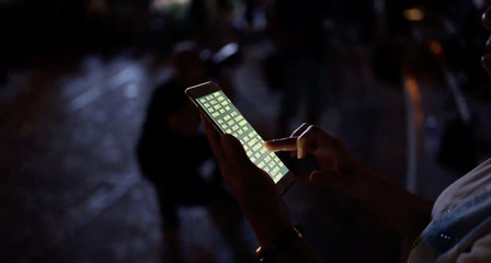 A protester holds a mobile phone displaying the lyrics to the Hong Kong anthem during the Mid-Autumn Festival in Hong Kong