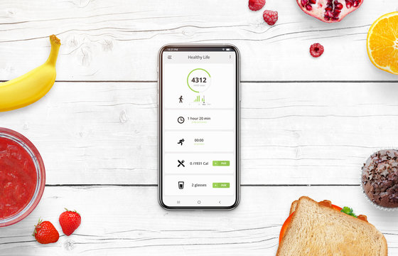 Phone on desk surrounded with food. Healthy life app concept with daily number of steps, number of calories burned, number of calories consumed and the amount of water.