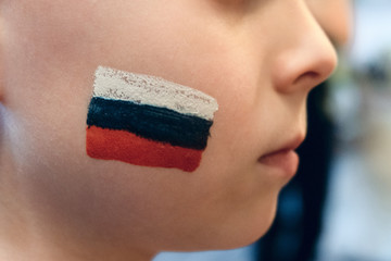 Child fan of the Russian national team. Boy with image of the flag of Russia on the cheek. Soft focus with limited depth of field.