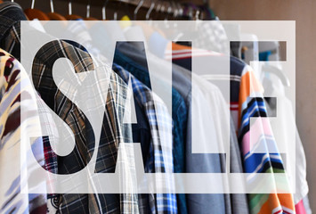 """An image of a """"SALE"""" writing on the background of clothes of different colors hanging on the coat hangers"""