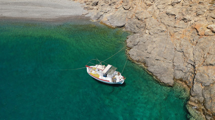 Aerial drone photo of traditional fishing boat docked in paradise beach of Kaminakia with emerald clear sea, Astypalaia island, Dodecanese, Greece