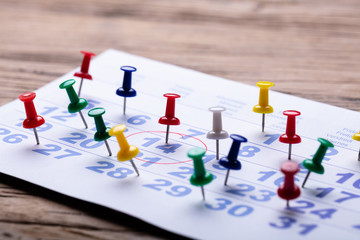 Fototapete - Calendar With Colorful Push Pins Over Wooden Desk