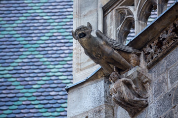 Elements of Gothic architecture. Grotesque, chimera and gargoyle sculptures on the facade of an ancient medieval cathedral. St. Stephen's Cathedral. Vienna. Austria