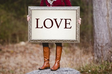 """Selective shot of a person holding a picture frame with word """"Love"""" written as a text"""