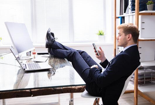 Lazy Man Using Phone At Work Desk