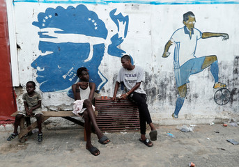Boys talks to each other as they sit in the street in Dakar