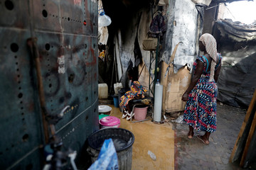 A woman and her daughter wait for their turn to use public washroom in Dakar