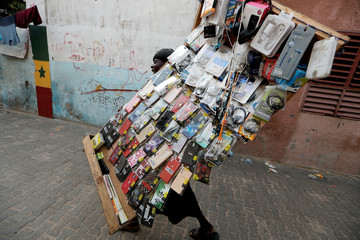 A street vendor carries goods for sale in Dakar