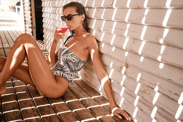 Gorgeous brunette girl in one-piece swimsuit and sunglasses thoughtfully drinking cocktail over wood background on beach