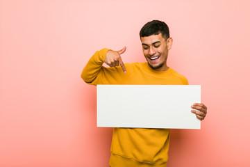 Young hispanic man holding a placard