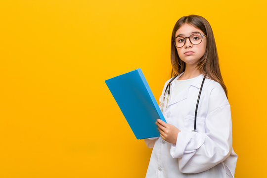 Little caucasian girl wearing a doctor costume