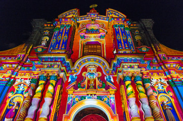 The facade of the Compania de Jesus church illuminated with colorful lights during the light festival, Quito, Ecuador.