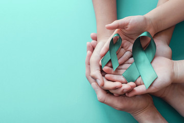 Adult and children hands holding Teal ribbons on blue background, Ovarian Cancer, cervical Cancer, anti bullying and sexual assault awareness