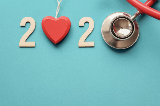 2020 wooden number with red stethoscope. Happy New Year for heart health and medical concept, life insurance business, New Year resolutions goal