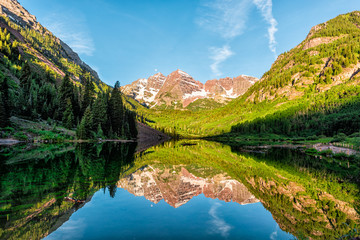Maroon Bells lake at sunrise panoramic view in Aspen, Colorado with rocky mountain peak and snow in July 2019 summer and vibrant light reflection on water